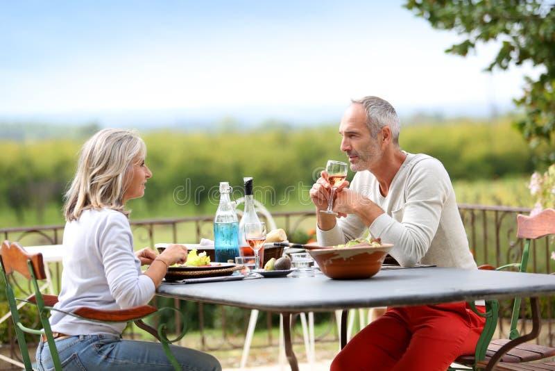 吃资深的夫妇在大阳台的午餐 库存图片
