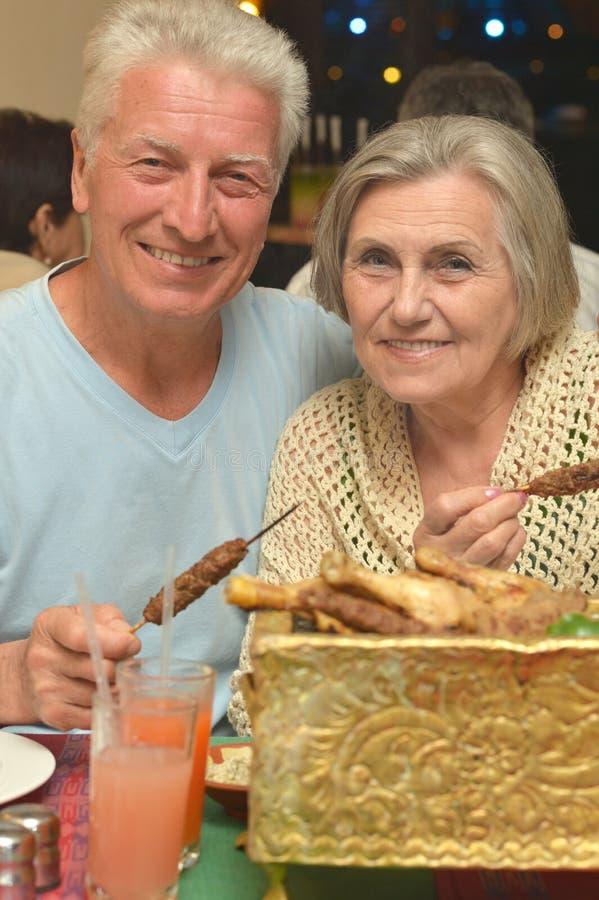 吃资深的夫妇晚餐 免版税库存图片