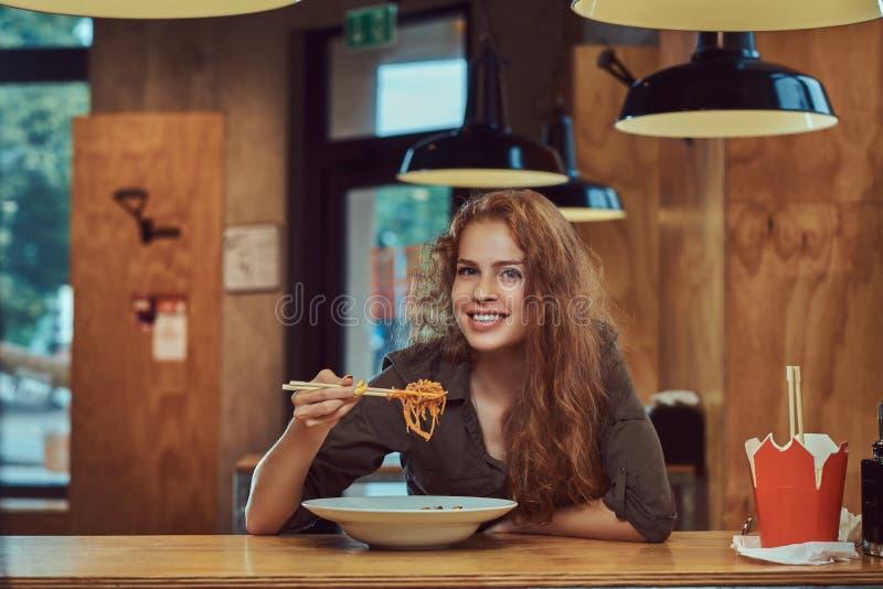 吃辣面条的年轻红头发人女性在一家亚洲餐馆 库存照片