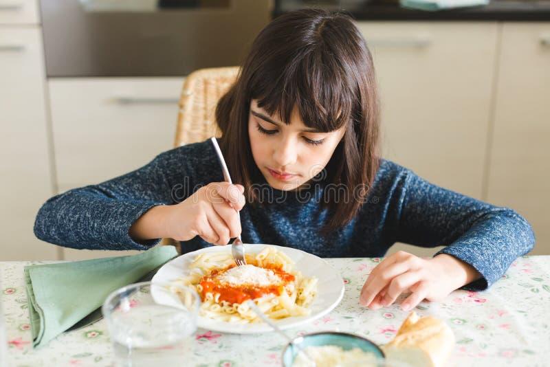 吃通心面用蕃茄和乳酪的小女孩 免版税图库摄影