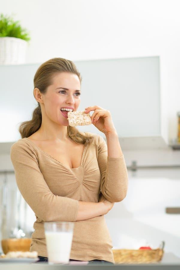 吃酥脆面包的少妇在厨房里 免版税库存照片