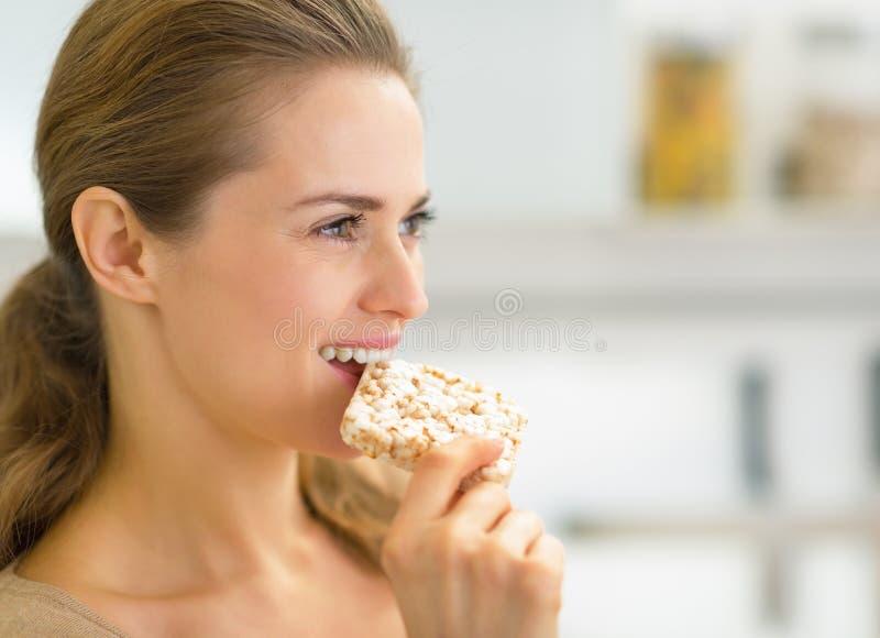 吃酥脆面包的少妇画象 免版税库存照片