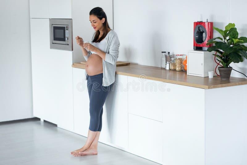 吃酸奶的美丽的怀孕的年轻女人,当在家时站立在厨房里 库存照片