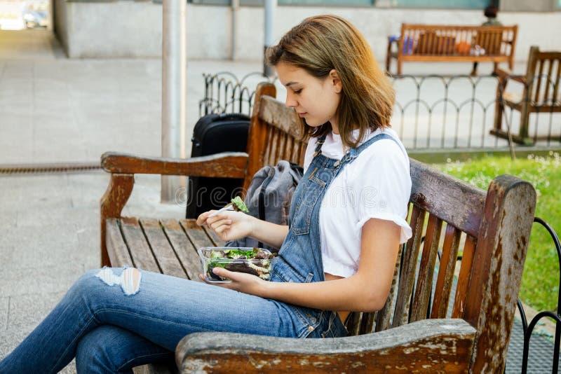 吃青少年的女孩健康午餐户外 免版税库存图片