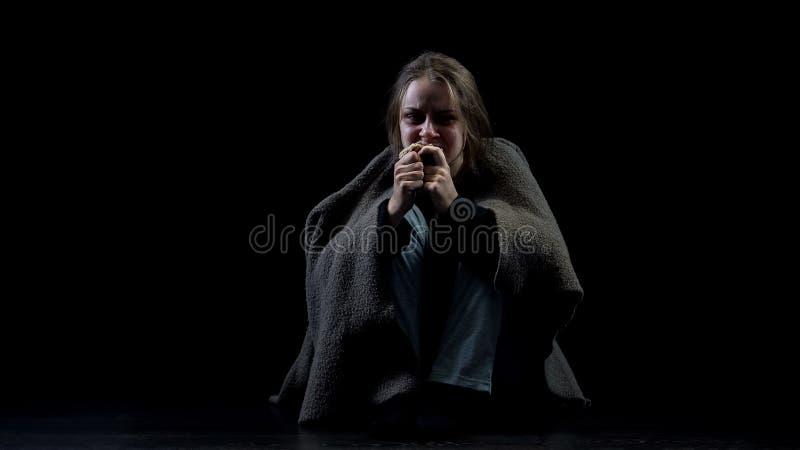 吃面包坐在黑暗中,恶习受害者的绝望的沮丧的无家可归的妇女 图库摄影