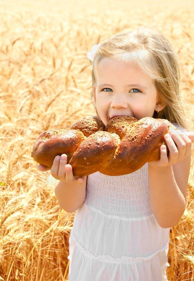 吃面包的逗人喜爱的小女孩 免版税库存图片
