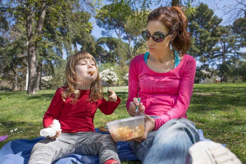 吃面团的孩子和母亲在公园 库存图片