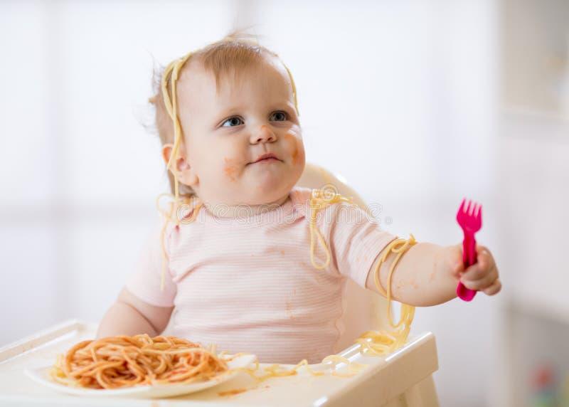 吃面条的滑稽的婴孩 肮脏的孩子女孩吃有叉子的意粉在家坐桌 免版税库存照片