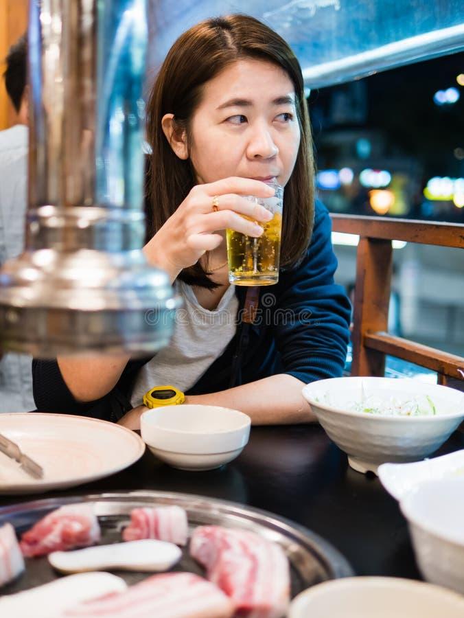 吃韩国样式猪肉BBQ的妇女 库存图片