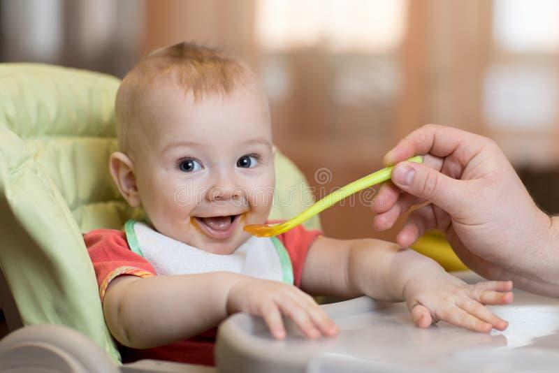 吃食物在父亲帮助下的婴孩 库存照片