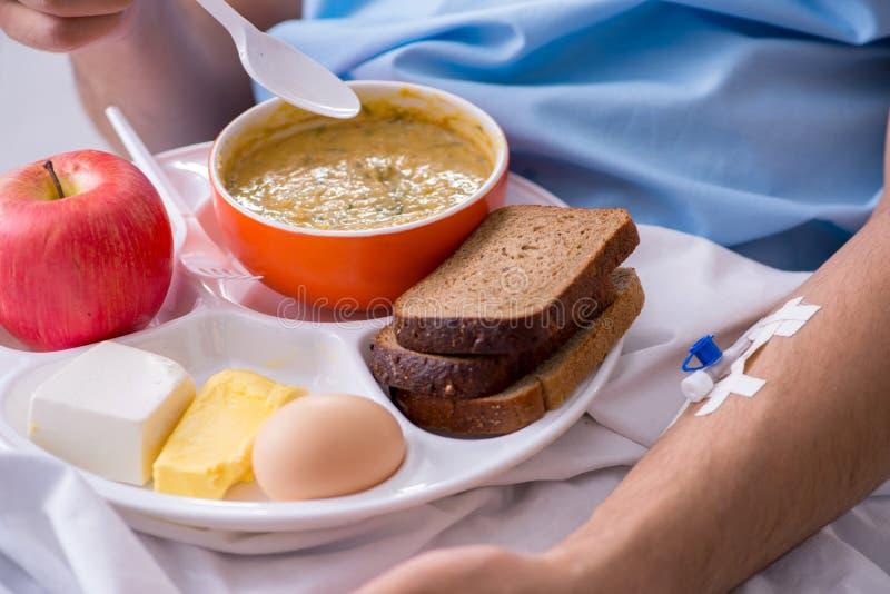 吃食物的男性患者在医院 免版税图库摄影