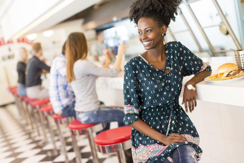 吃饭的客人的年轻黑人妇女 免版税库存图片