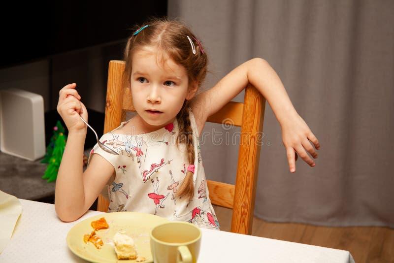吃饭的小女孩手拿叉子,草率、粗心、轻松地坐在椅子上, 免版税库存图片