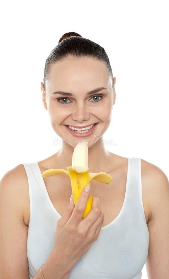 吃香蕉的快乐的适应妇女 库存图片