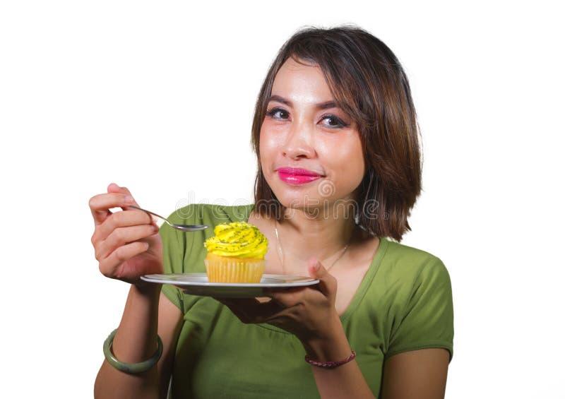 吃鲜美和可口黄色含糖的杯形蛋糕的年轻美丽和愉快的西班牙妇女摆在糖a的被隔绝的背景 免版税图库摄影