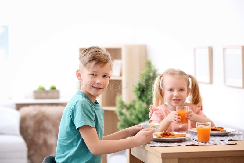 吃鲜美敬酒的面包用果酱的可爱的小孩 库存照片