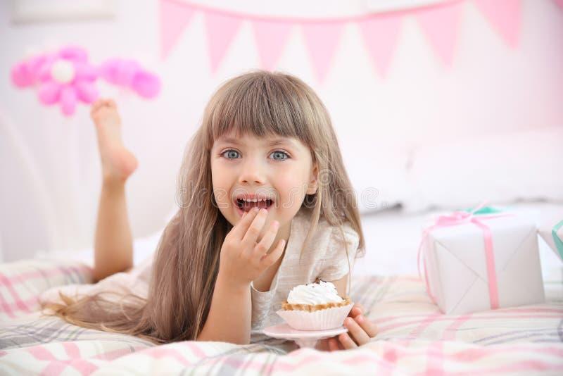 吃鲜美蛋糕的逗人喜爱的生日女孩,当说谎在床上时 免版税库存图片