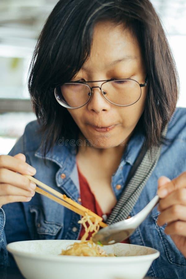 吃鸡蛋面用酥脆猪肉的妇女从筷子和遇见 免版税库存照片