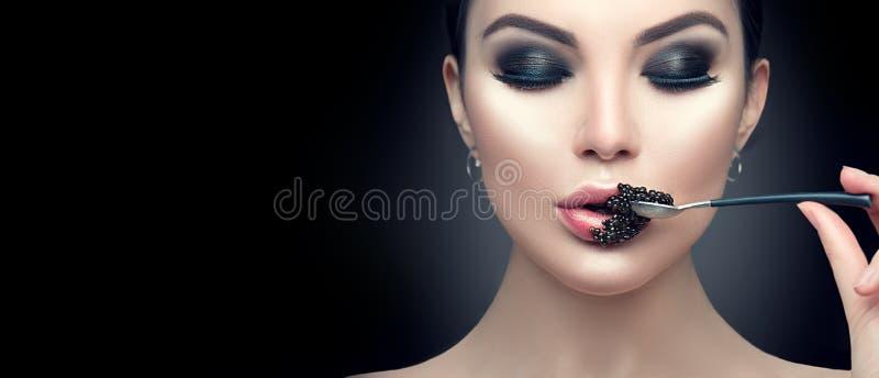 吃黑鱼子酱的美丽的时装模特儿妇女 秀丽女孩用在她的嘴唇的鱼子酱 免版税库存照片