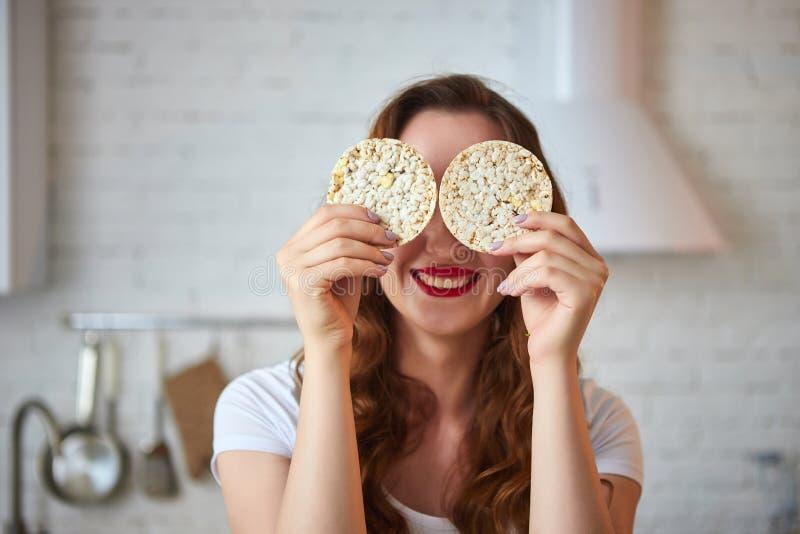 吃黑麦薄脆饼干酥脆面包的年轻女人在厨房里 r 健康,秀丽,饮食概念 库存照片