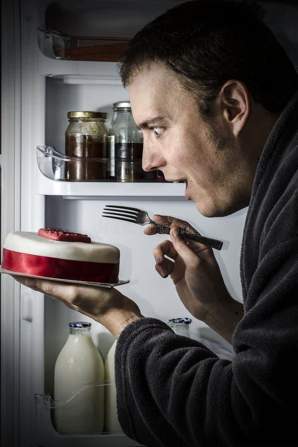 吃从冰箱的蛋糕 免版税图库摄影