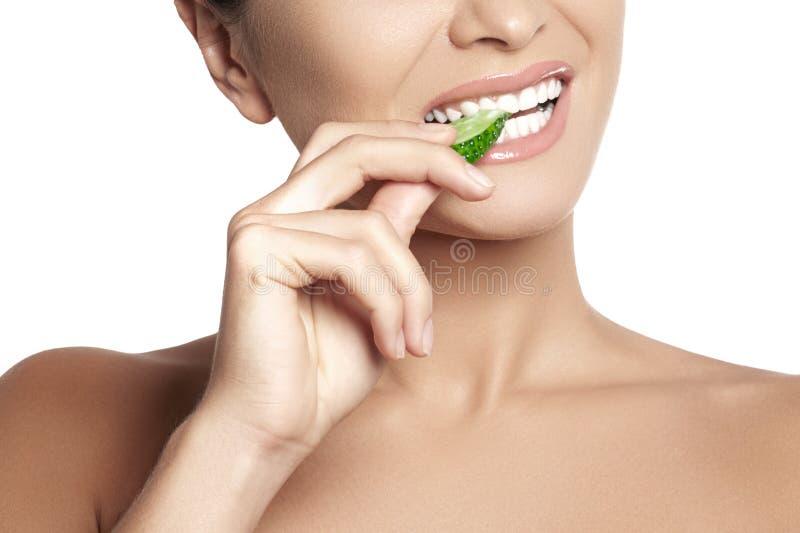 吃黄瓜的愉快的少妇 与白色牙的健康微笑 免版税库存图片
