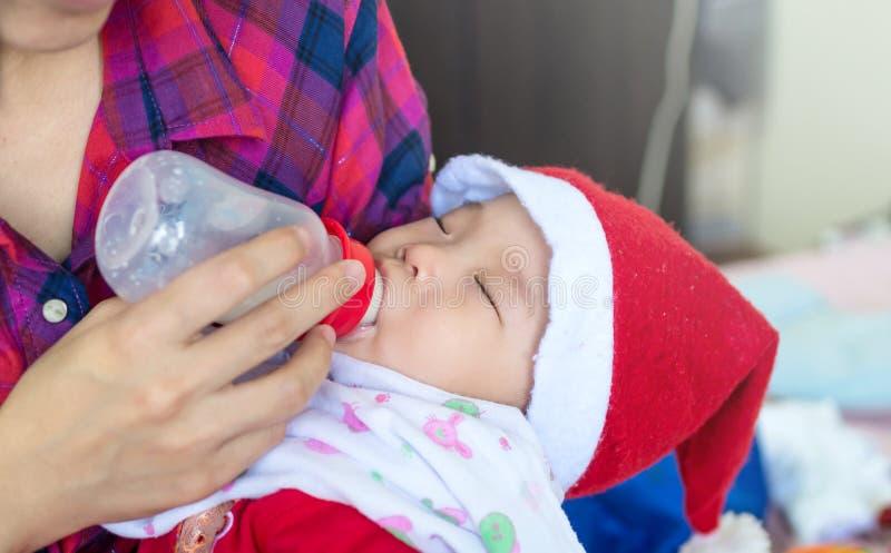 吃从瓶的婴孩牛奶在母亲哺养她新出生的Bab 免版税库存照片