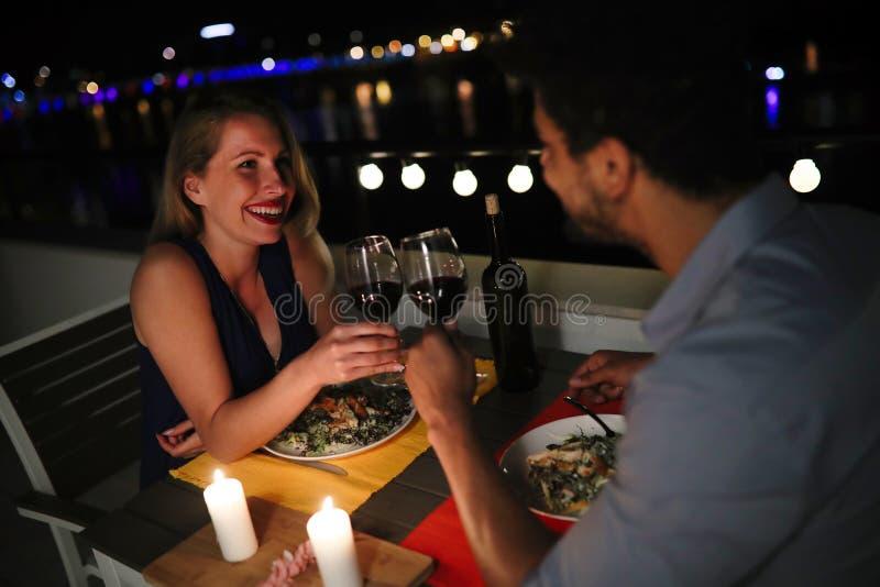 吃年轻美好的夫妇在屋顶的浪漫晚餐 库存照片