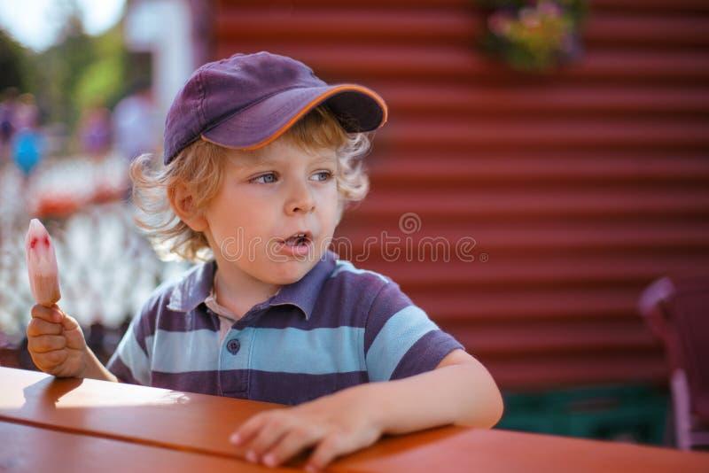 吃黄色冰淇凌的小白肤金发的男孩 免版税库存照片