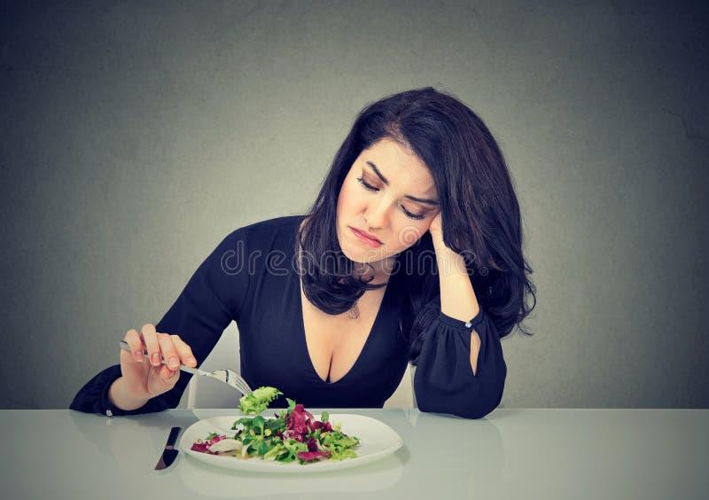 吃绿色散叶莴苣的生气的妇女疲倦了于饮食制约 免版税图库摄影