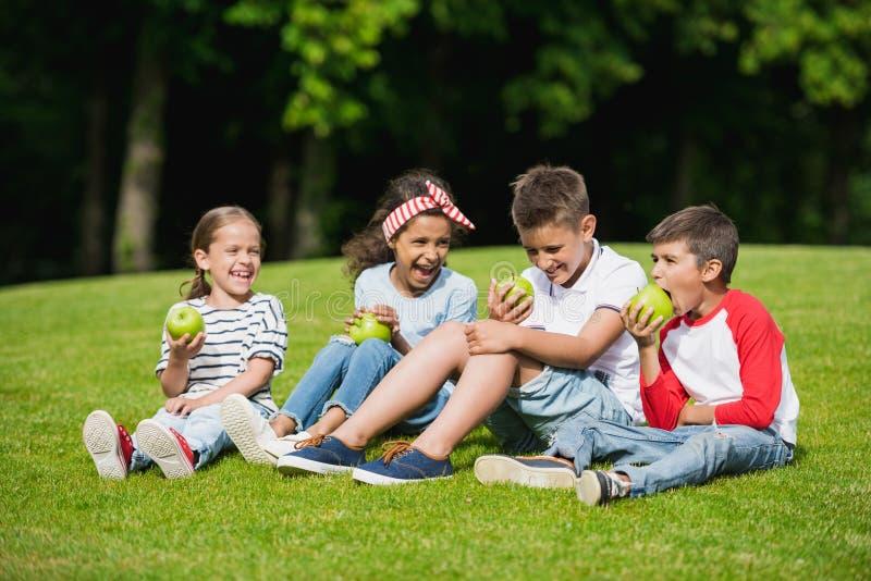 吃绿色苹果的不同种族的孩子,当一起坐绿草时 免版税库存图片