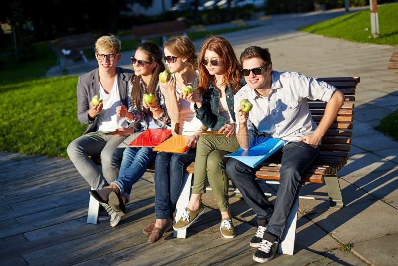 吃绿色苹果的小组愉快的学生 免版税库存照片