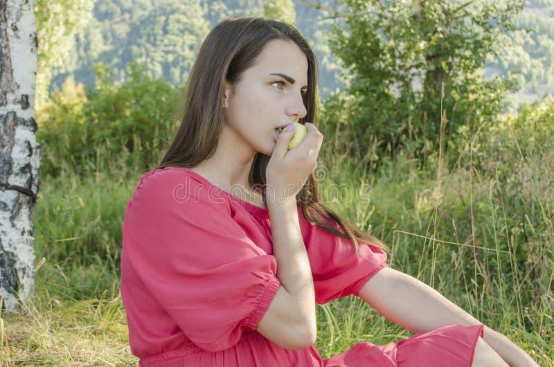 吃绿色苹果计算机的女孩 图库摄影