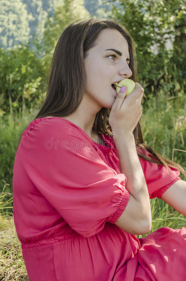 吃绿色苹果计算机的女孩 免版税库存图片