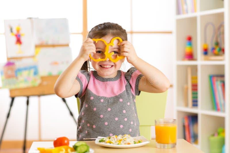 吃素食主义者食物的儿童女孩获得乐趣在幼儿园 免版税库存图片