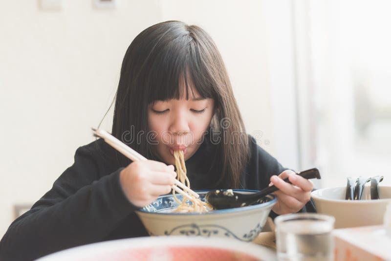 吃chashu拉面的亚裔女孩在日本餐馆 库存图片