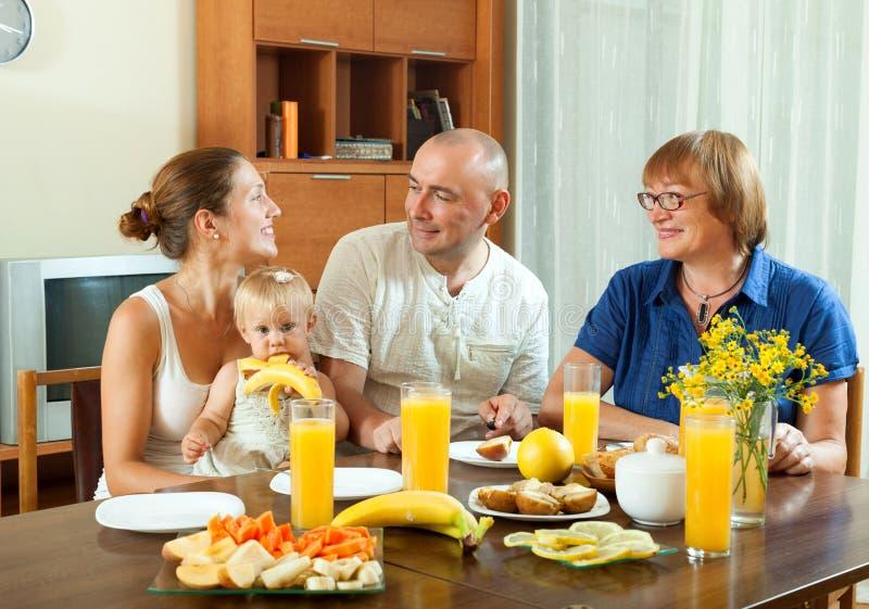 吃friuts和drinkin的愉快的微笑的三世代家庭 库存照片