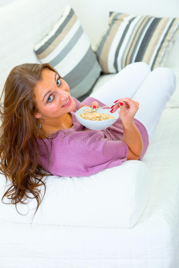 吃muesli坐的微笑的沙发妇女 库存图片