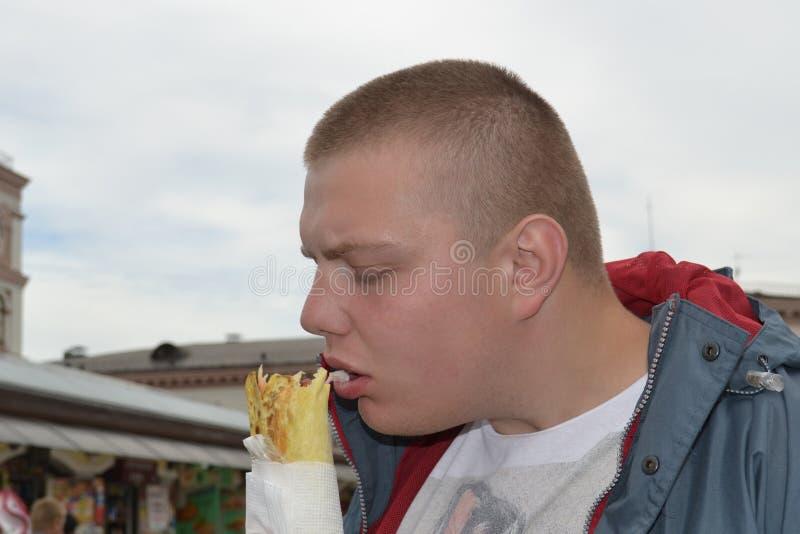 吃shawarma高兴地一个滑稽的人的画象 库存照片
