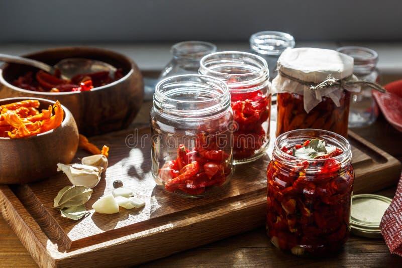 各式各样的蕃茄用草本和海盐在橄榄油在一个玻璃瓶子 免版税库存图片