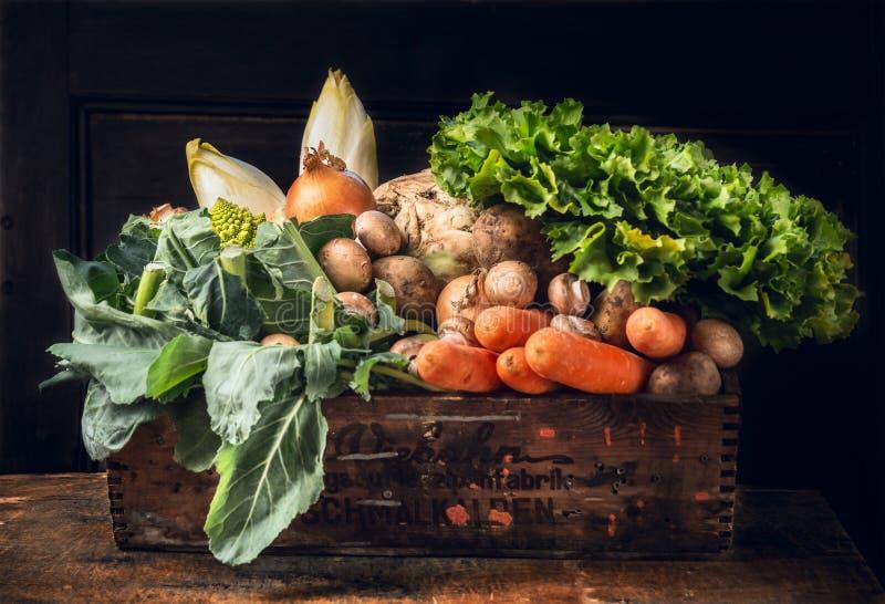各种各样在老箱子的新鲜蔬菜在黑暗木 免版税库存照片