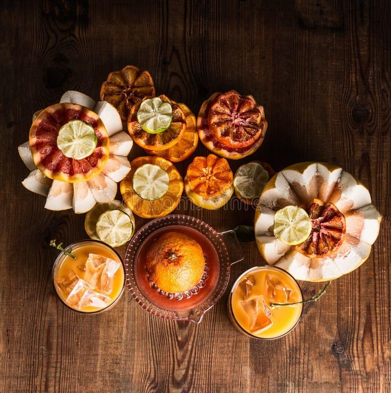 各种各样的五颜六色的柑橘水果用在玻璃的新鲜的被紧压的柑橘汁与在桌上的冰块与成份:桔子, 免版税库存图片