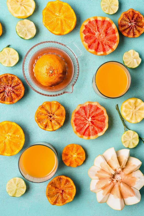 各种各样的五颜六色的热带柑橘水果用在玻璃和柑橘剥削者的汁液在浅兰的背景,顶视图,平的位置 免版税库存照片