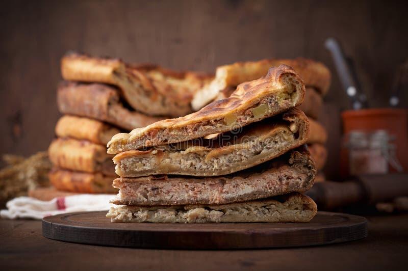 各种各样的传统奥塞梯肉馅饼用牛肉、鸡和三文鱼在木背景 库存照片