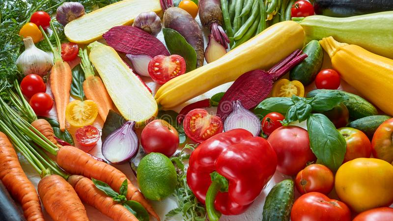各种各样的健康素食食物背景 未加工的蔬菜、草本和香料在白色厨房用桌上:西红柿,夏南瓜 库存图片