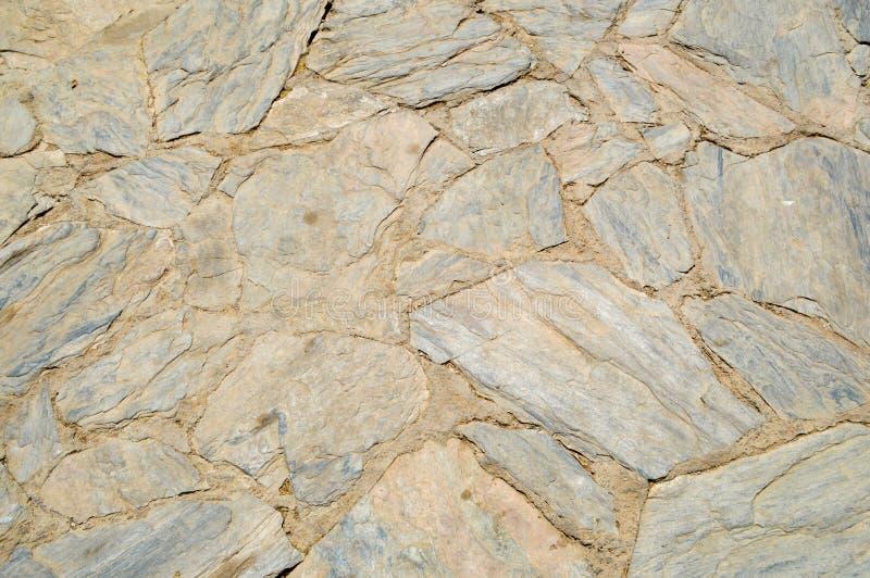 各种各样的参差不齐的石头,有堆的鹅卵石粗糙的老,古老褐色纹理在bristchatku的地板放置了 免版税库存图片
