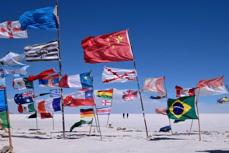 各种各样的国家旗子在撒拉族de Uyuni,玻利维亚 库存照片