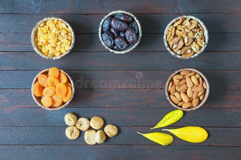 各种各样的坚果和干果子核桃,杏仁,杏干,葡萄干,日期结果实,在黑暗的木背景的无花果 平的位置 免版税图库摄影