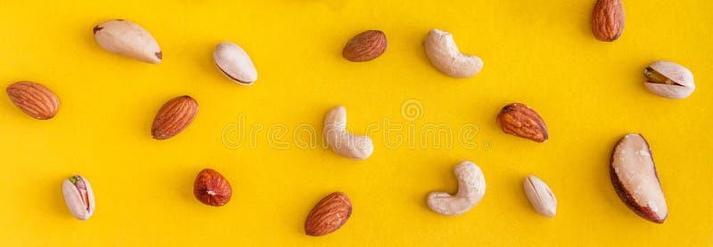 各种各样的坚果在黄色背景驱散 r o r 免版税库存图片
