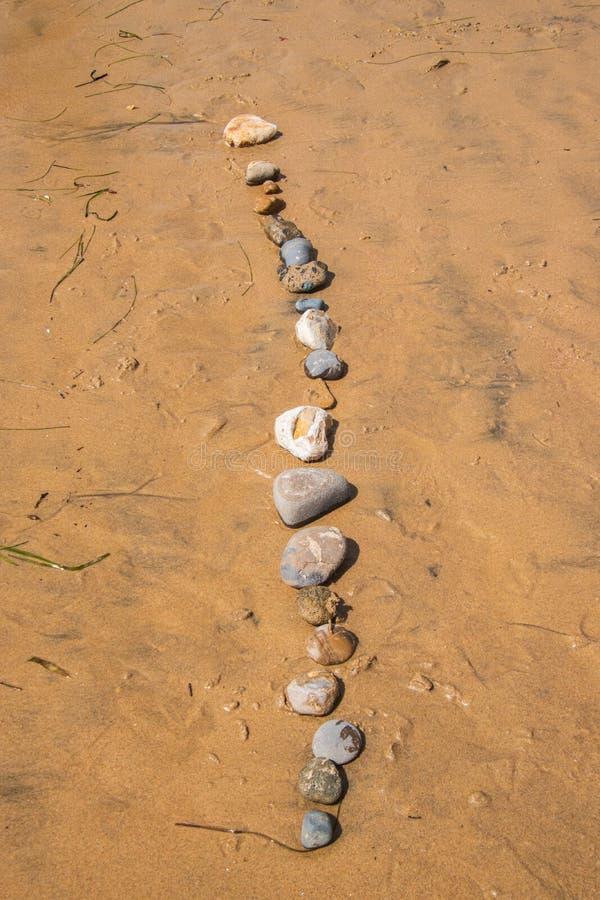 各种各样的大小、形状和纹理二十块石头在一条垂直线在沙子在海滩 免版税库存照片